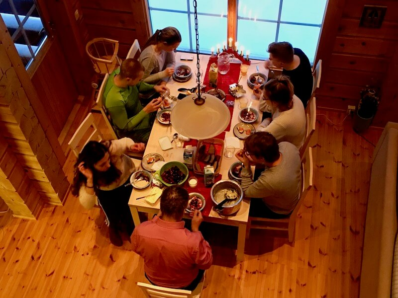 Family having a Christmas Eve dinner at Syöte in a log cabin.